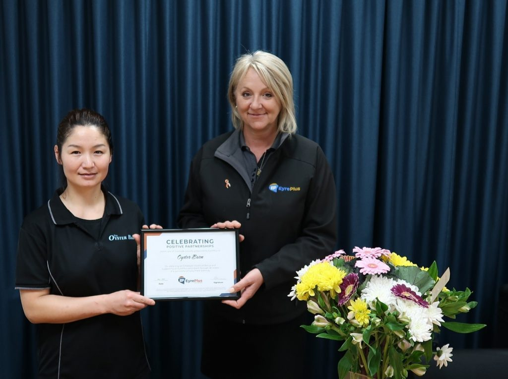 Ceduna Oyster Barn Staff Member, Suvdaa, and Nat, TRACQS Employment Consultant, holding a TRACQS certificate and a bunch of flowers